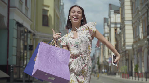 Cute cheerful young woman with shopping bags. Girl with headphones and cell Footage