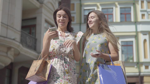 Two happy girlfriends after shopping with shopping bags texting on the cellphone Footage