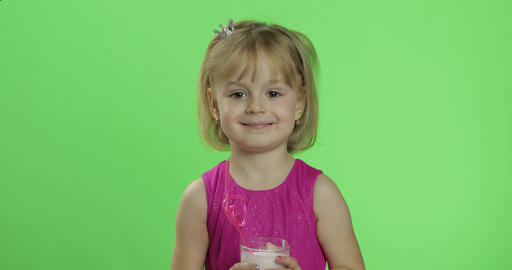 Happy young child waving in pink dress with milkshake cocktail. Chroma Key Live Action