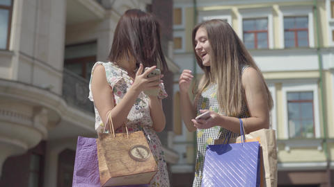 Two happy girlfriends after shopping with shopping bags... Stock Video Footage