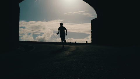 Tracking shot of a woman silhouette running out from tunnel towards the sunlight Footage