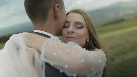 Groom with bride having fun on a mountain hills. Wedding couple hugging Footage