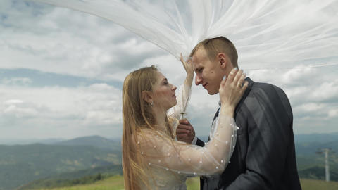 Groom with bride having fun on a mountain hills. Wedding couple. Happy family Footage