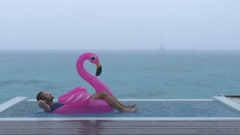 Vacation rain - funny video of man on flamingo float in luxury pool Footage