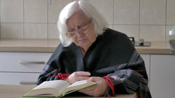 Old woman is reading thick book Live Action