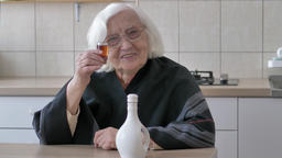 Old woman is celebrating with a glass of alcohol Footage