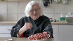 Old woman is showing plate with red gooseberry Footage