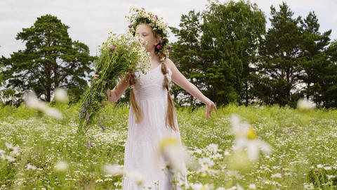 Young teenager girl in wreath sniffing flowers bouquet on blooming field Footage