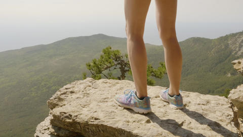 Traveling girl standing on mountain edge. Happy young woman straightened Footage