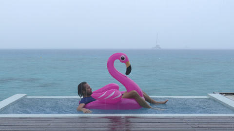 Funny fail video in vacation rain of man on flamingo float in luxury pool Footage