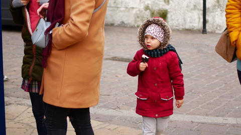 The girl eats ice cream on the street. Autumn, cool weather Live Action