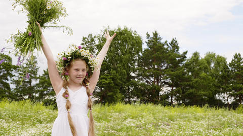 Teenager girl in flower wreath raised up hands with meadow flowers on green Live Action
