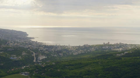 Panoramic view modern city in valley on sea shore from mountain peak. Amazing Footage