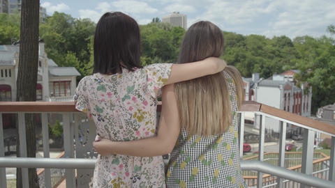 Two attractive girls standing outdoors together hugging…, Live Action