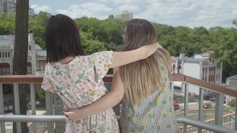 Two attractive girls standing outdoors together hugging and talking, admiring Footage