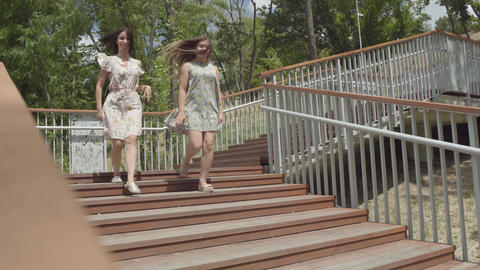 Two attractive girls wearing summer dresses running down the stairs in the city Footage