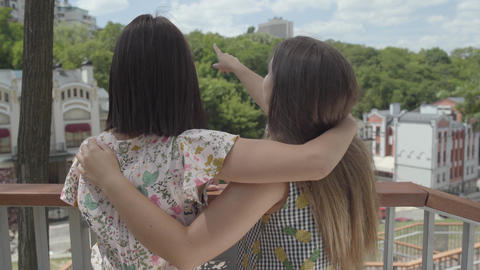 Two adorable young woman standing outdoors together hugging and talking Footage