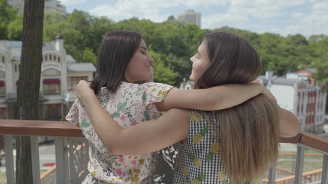 Two cute young woman standing outdoors together hugging and talking, admiring Footage