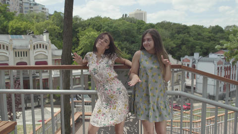 Two attractive girls dancing outdoors together in front of beautiful cityscape Footage