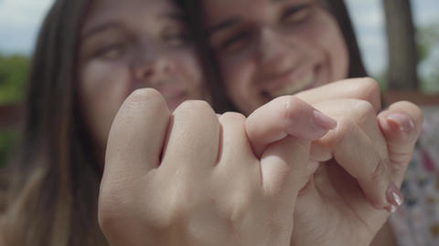 Close-up of attractive girls taking each other's little fingers and smiling Footage