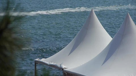 yacht traveling on water ripples surface & white pavilion shed Footage