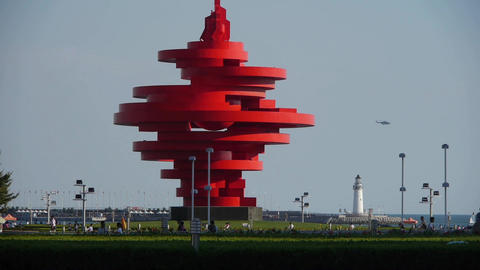 Red torch sculpture & Seaside lighthouse.This public... Stock Video Footage