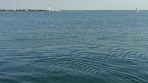 water surface.Sailboat sailing in sea,relying on lighthouse dam at dusk Footage