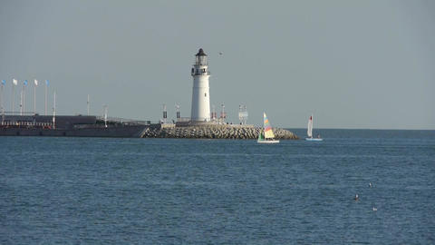 Sailboat sailing in sea,relying on lighthouse dam at... Stock Video Footage