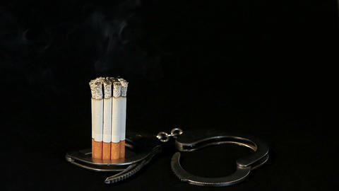 smoldering cigarette in handcuffs on black background,... Stock Video Footage