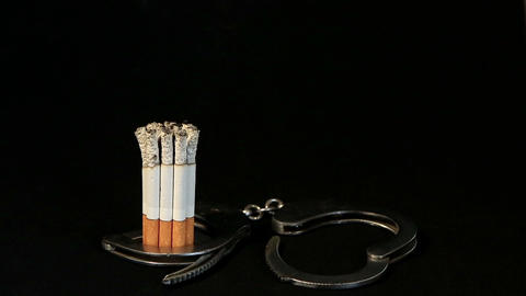 smoldering cigarette in handcuffs on black background, Timelapse Footage