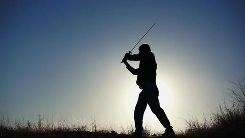 Silhouette of Guy Practicing With Sword Stock Video Footage