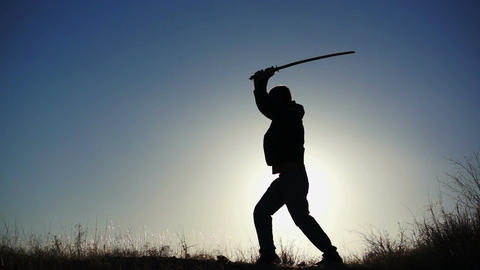 Silhouette of Guy Practicing With Sword Footage