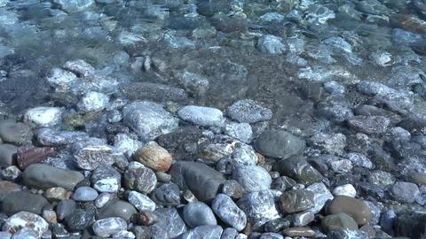 Sea waves roll on wet pebble beach. 4K Footage