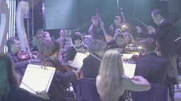 The conductor conducts the large orchestra on stage Footage