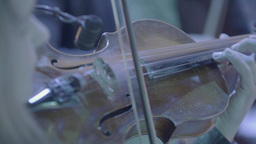 Violin in hands of the girl-violinist while playing in the orchestra .Close-up Footage