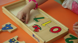 kid playing with geometric pieces board game Footage