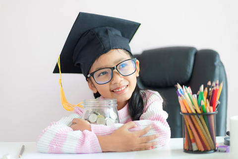 Little Asian girl wearing graduate hat putting the coin into clear glass jar 016 フォト