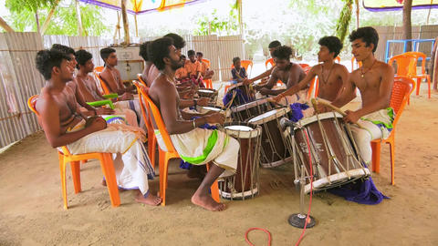 Indian man an playing on a Chenda Melam (Temple Musics playing with Traditional Drums) in Temple Footage