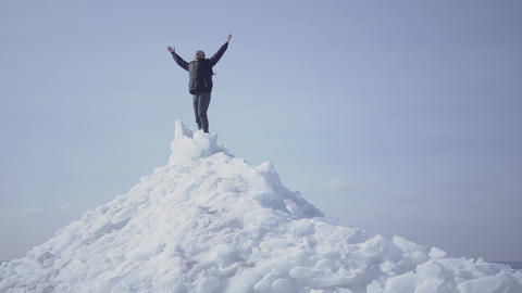 Emotional happy man in warm coat standing on the top of glacier throwing up his Live Action