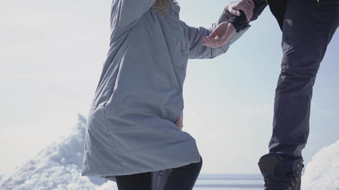 Handsome blond bearded man giving hand to attractive young woman helping her to Footage
