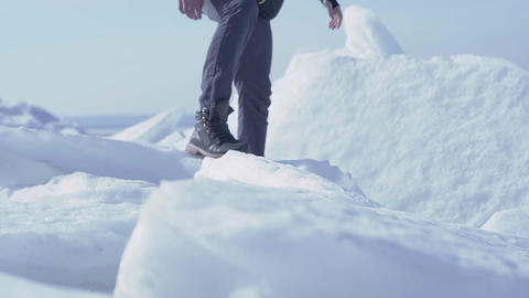 Unrecognized man climbed to the top of ice glacier in cold winter weather. Slow Footage