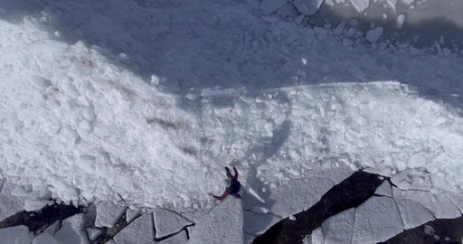 Aerial dron view of young active happy man walking on the ice glaciers near Footage