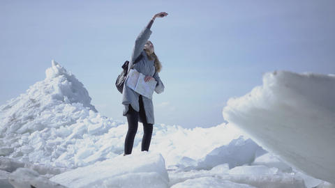 Pretty young woman in warm jacket walking on the glacier, holding her cellphone Footage