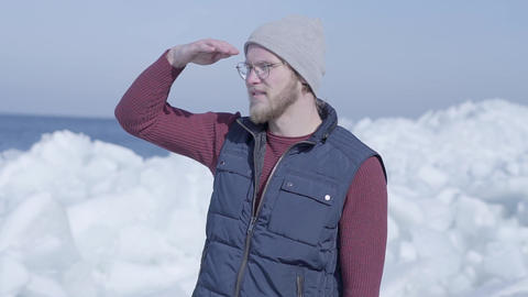 Young handsome man tourist focused on something near cold ice snowing glacier Footage
