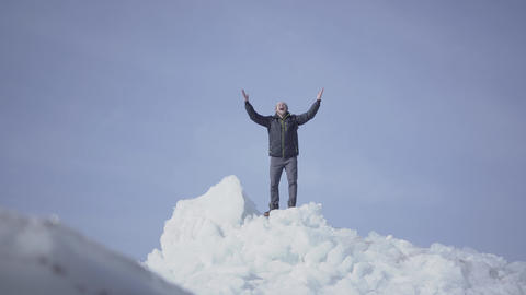 Emotional happy man in warm coat standing on the top of glacier throwing up his Footage