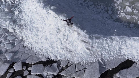 Aerial dron view of young active happy man staying on the ice glaciers near Footage