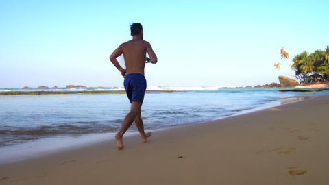 barefoot athlete runs along wet sand at ocean slow Footage