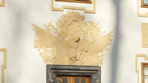 Facade of beige house with door and beautiful coat of arms sculpted on wall Footage