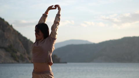 Sport girl stretches her hands against the background of , the sea, slow motion Footage