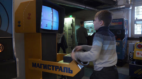 A cute teen boy practices his skills on a car-racing slot machine in museum Footage